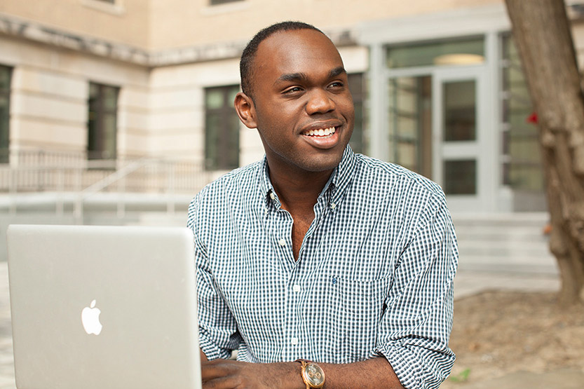 A man smiles while looking away from his laptop while outside on campus