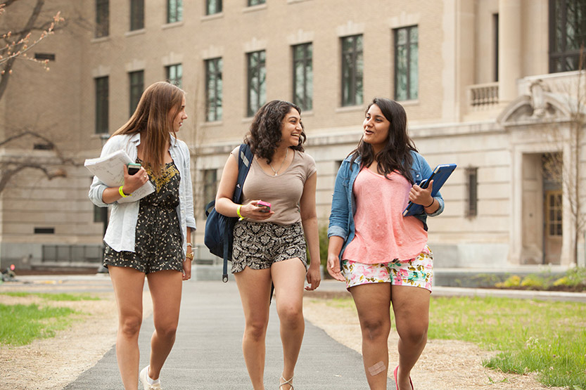 Three female students walking together on campus