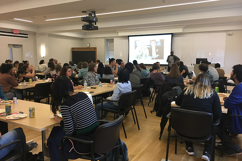 A room of students eating at tables with a speaker at a podium discussing a projected image