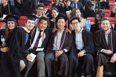 A group of students sit together before graduation