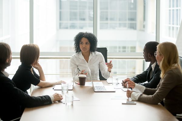 Female boss leading diverse corporate team meeting in boardroom