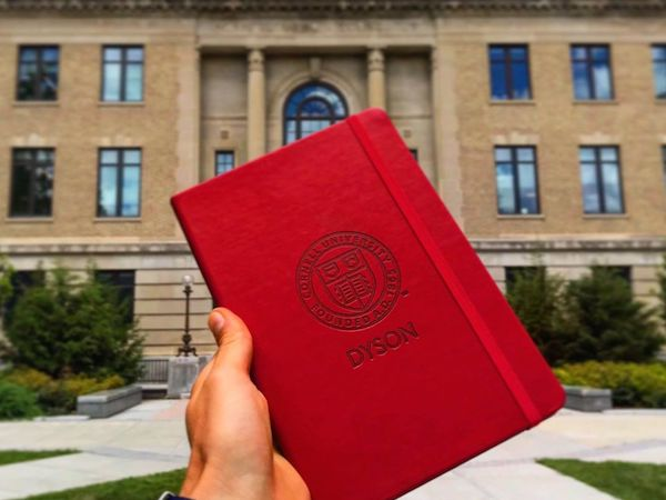 Holding a Dyson notebook next to Warren Hall