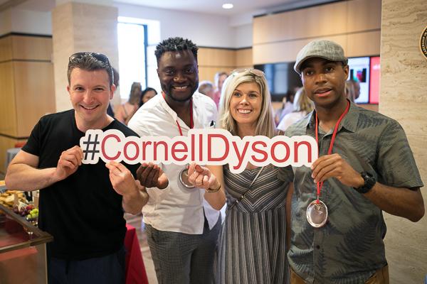 Alumni smile holding a #CornellDyson sign