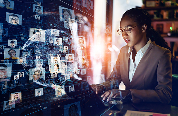 Business woman of color typing on a laptop with a hologram of a globe and connections to many headshots in the foreground