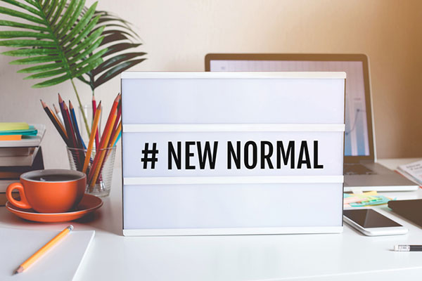"stock photo: ""new normal"" sign in the middle of a work desk with a cup of colored pencils, a plant, a laptop, and a cell phone"