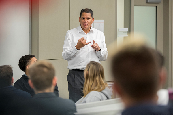 Reggie addresses students in the front of a classroom