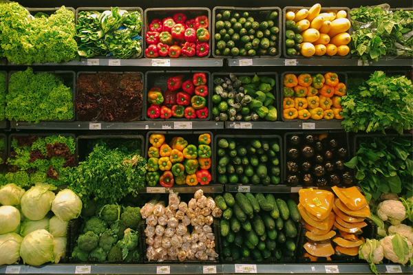 rows of vegetables in a grocery store cooler
