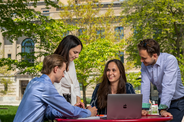 group of students having a discussion over a laptop