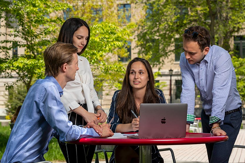 Cornell CEMS students gathered around a laptop outdoors at a table