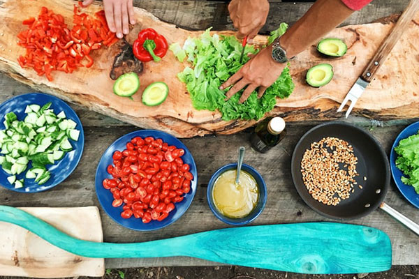 Components of a meal in preparation: cut up vegetables in bowls and on a cutting board along with a bowl of grains and of beans and a sauce. Also shows a person's hands cutting up a green leafy vegetable